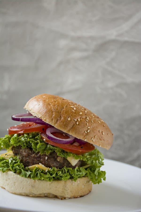 Свежий домодельный бургер на белой плите Нездоровая еда стоковое фото rf