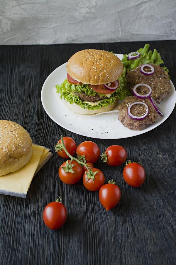 Свежий домодельный бургер на белой плите Нездоровая еда стоковое изображение rf
