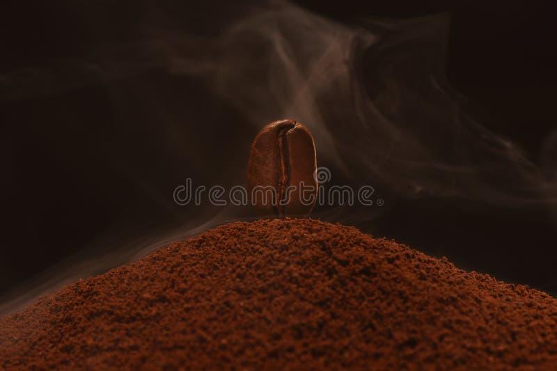 Свежий жареный кофейный боб стоит на полосе горстки кофе в дыме Черный фон Почтовая карта, баннер стоковая фотография rf