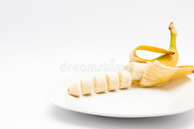 Свежий, здоровый отрезанный банан на белой изолированной плите стоковые фотографии rf