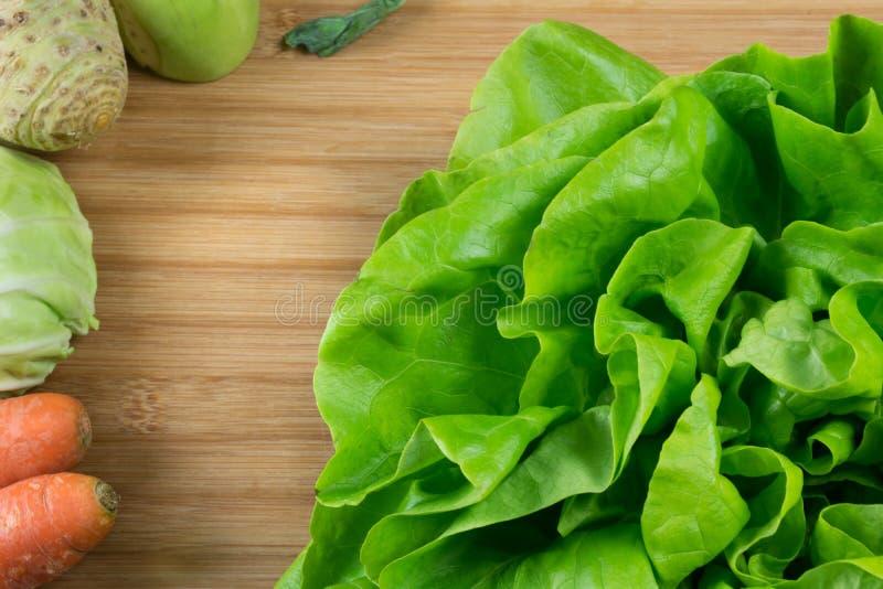 Свежий зеленый салат на доске трески и свежие овощи, морковь, капуста, сельдерей и кольраби на стороне стоковое фото