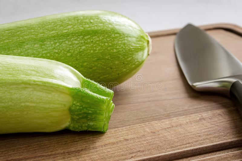 Свежий зеленый цукини 2 и профессиональный нож шеф-повара на коричневой деревянной разделочной доске Сварите дома Свежие овощи, и стоковая фотография rf