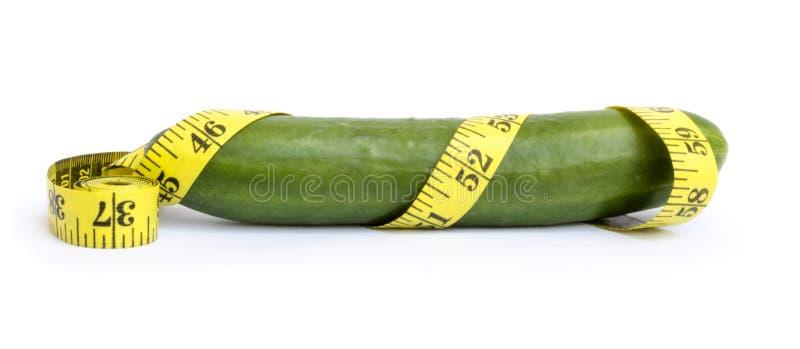 Свежий зеленый огурец обернутый в измеряя ленте стоковое изображение
