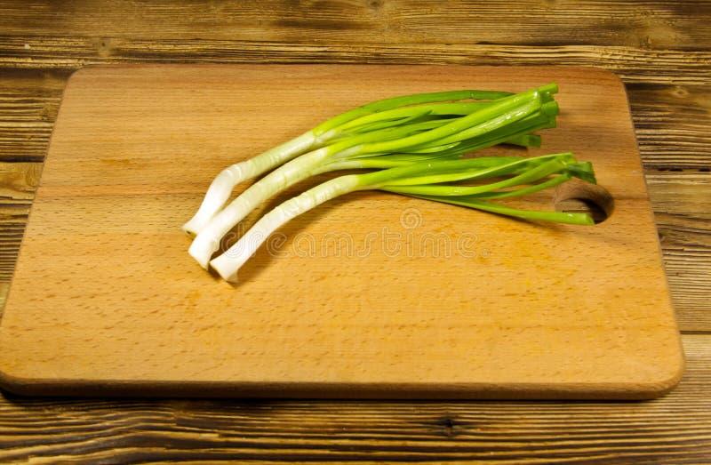 Свежий зеленый лук на разделочной доске на деревянном столе стоковые изображения rf