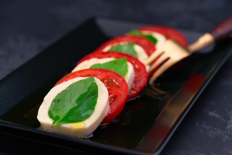 Свежий итальянский caprese салат с моццареллой и томатами на темной плите стоковая фотография rf