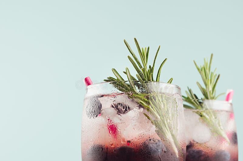 Свежий коктейль с кубами льда, голубика ягоды, розмариновое масло, сол стоковое изображение