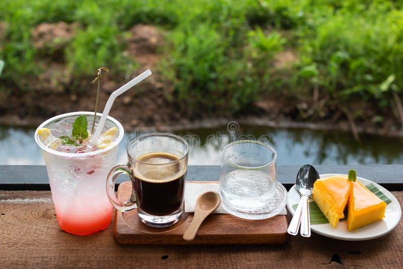 Свежий кофе в стеклянных и оранжевых торте и соке Lychee смешанном стоковая фотография rf