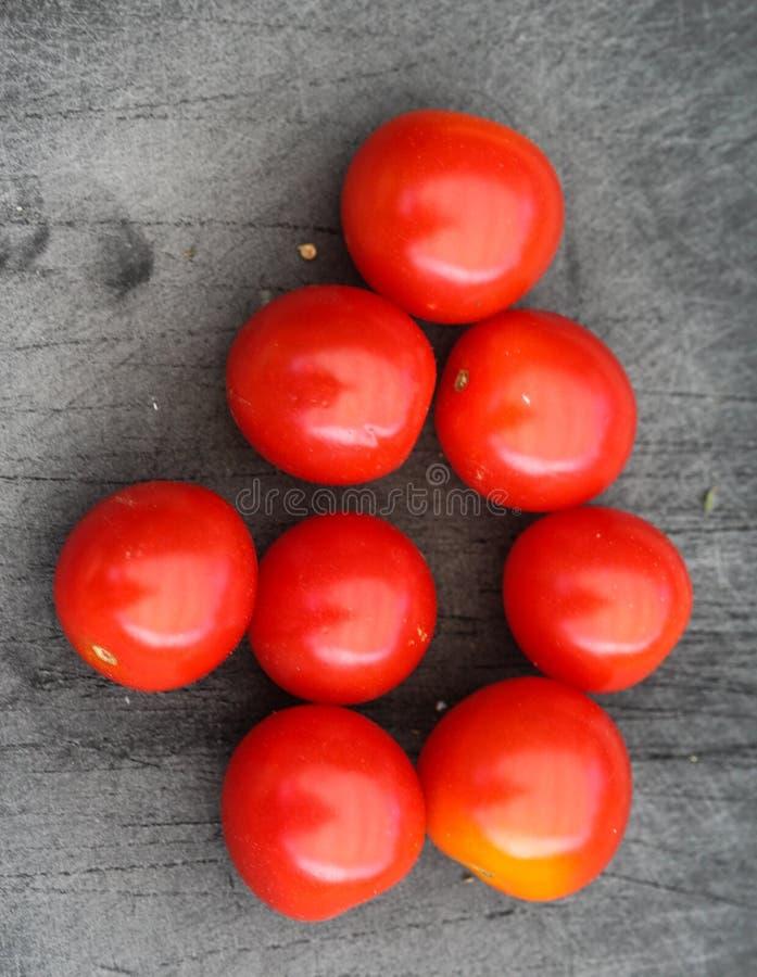 Свежий красный томат вишни на черной предпосылке разделочной доски стоковое изображение