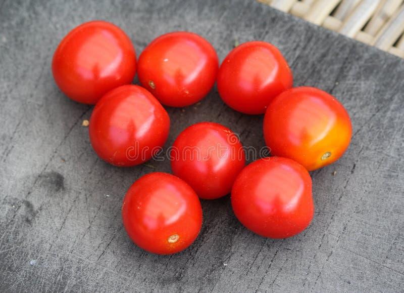 Свежий красный томат вишни на черной предпосылке разделочной доски стоковые изображения rf
