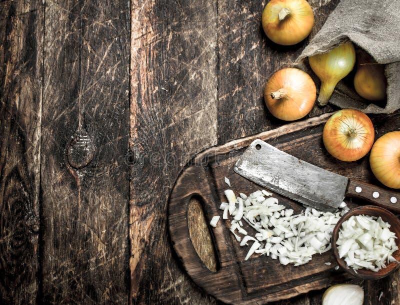 Свежий лук с старым топориком на разделочной доске стоковое изображение
