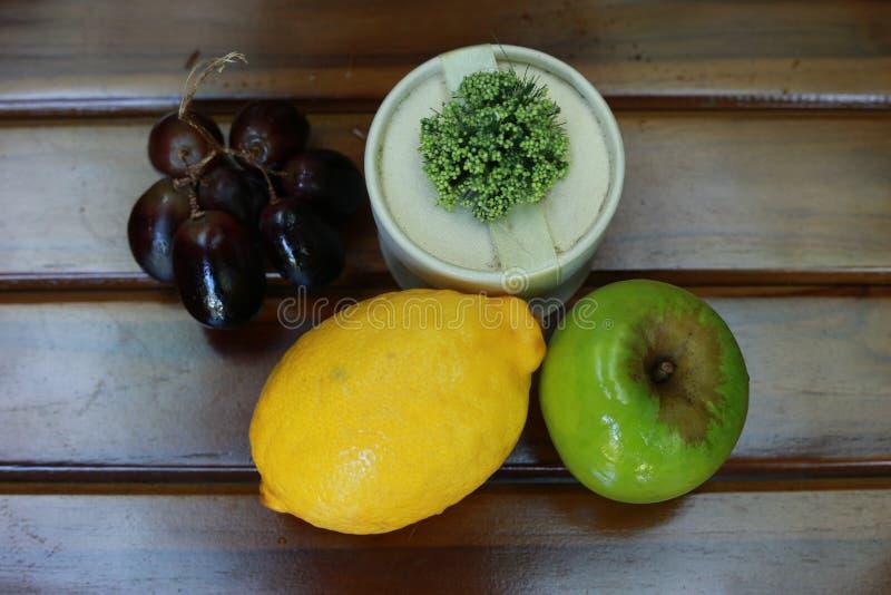 Свежий намочите плодоовощи: лимон, зеленое яблоко и виноградины с украшением на деревянной предпосылке стоковое фото rf