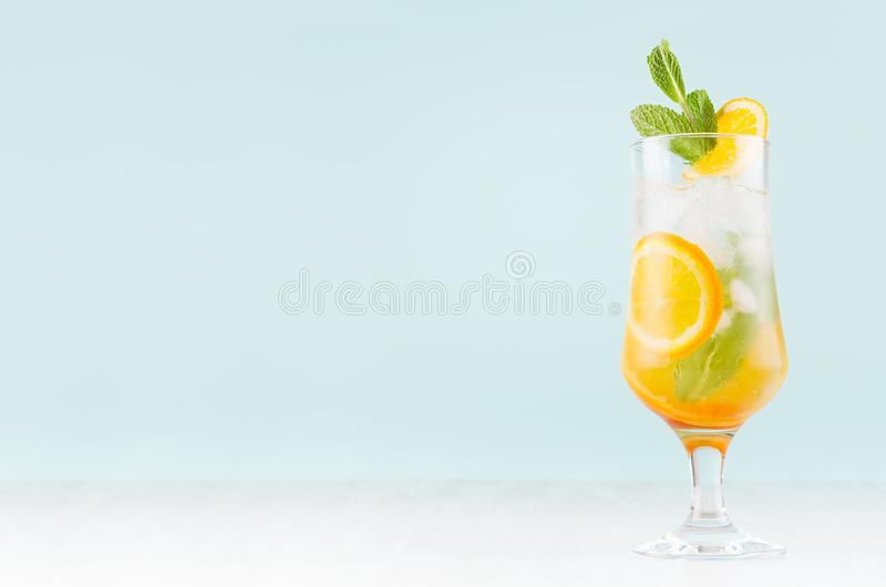 Свежий оранжевый коктейль с плодами кусков, мятой, соломой, кубами льда в misted стекле на белой деревянной таблице и голубой сте стоковые фото