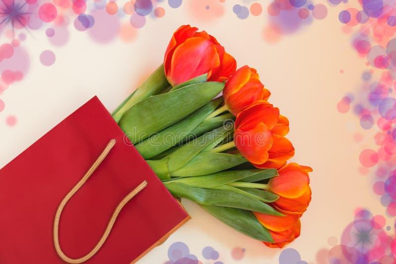 Свежий оранжевый тюльпан цветет в бумажной сумке на бежевой предпосылке стоковая фотография rf