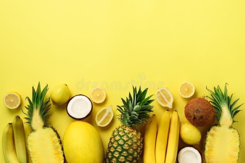 Свежий органический желтый цвет приносить над солнечной предпосылкой Monochrome концепция с бананом, кокосом, ананасом, лимоном,  стоковое изображение rf