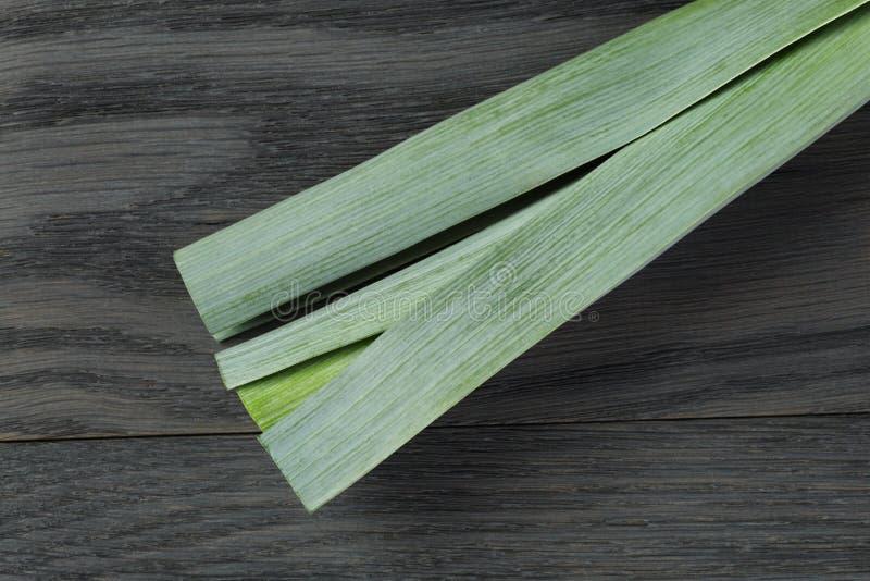 Свежий органический лук-порей на винтажной таблице дуба стоковое фото