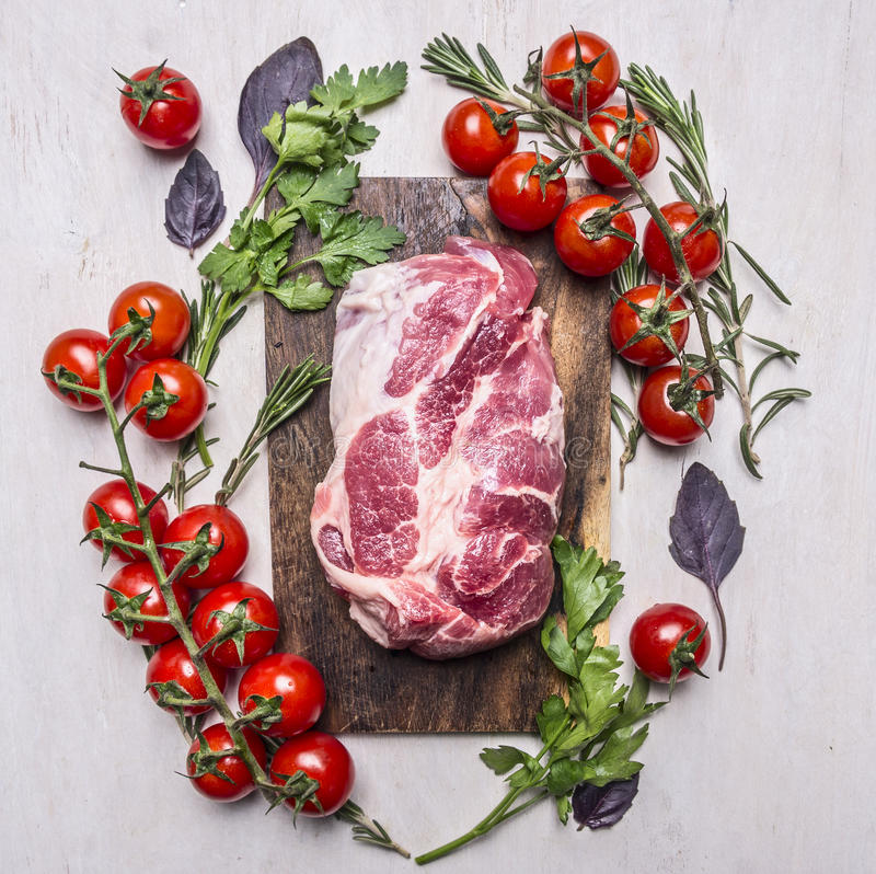 Свежий, очень вкусный сырцовый стейк свинины на разделочной доске с овощами, конце взгляд сверху предпосылки трав деревянном дере стоковые изображения