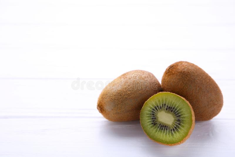 Свежий плод кивиа и половина кивиа на белой деревянной предпосылке стоковые фото