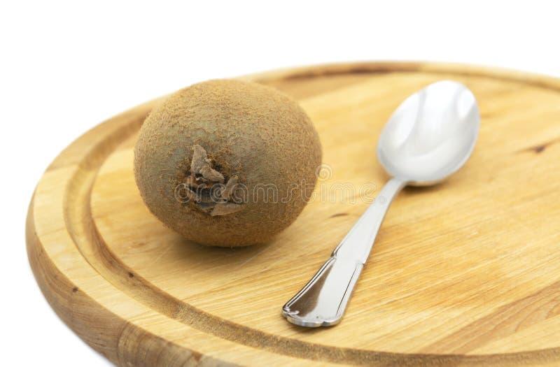 Свежий плод кивиа с ложкой на деревянной доске стоковые изображения