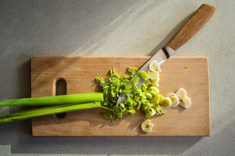 Свежий прерванный лук-порей на деревянной доске и ноже стоковая фотография rf