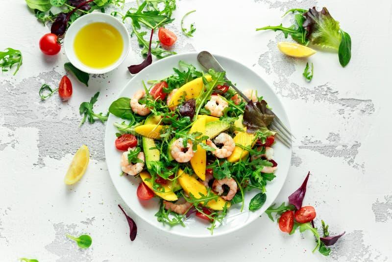 Свежий салат авокадоа, креветок, манго с смешиванием зеленого цвета салата, томаты вишни, травы и оливковое масло, шлихта лимона стоковые изображения rf