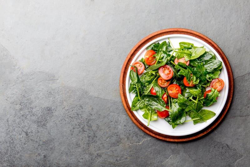 Свежий салат лета с шпинатом младенца и вишней томатов Взгляд сверху, космос экземпляра Предпосылка серого цвета шифера стоковое изображение rf