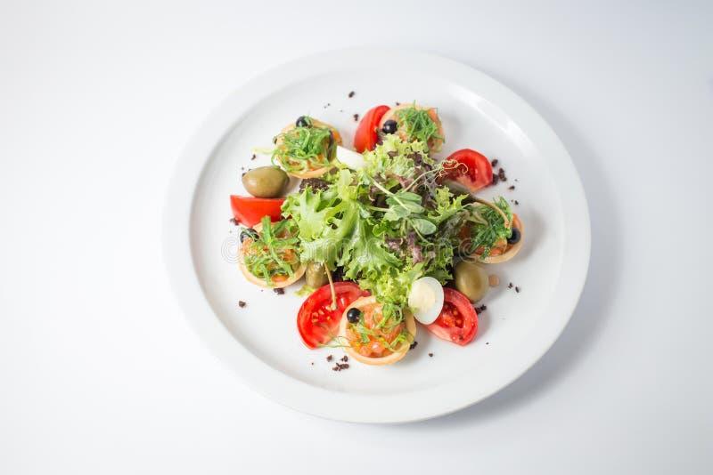 Свежий салат с семгами, оливками, зеленым цветом, томатами и яичками триперсток стоковое фото