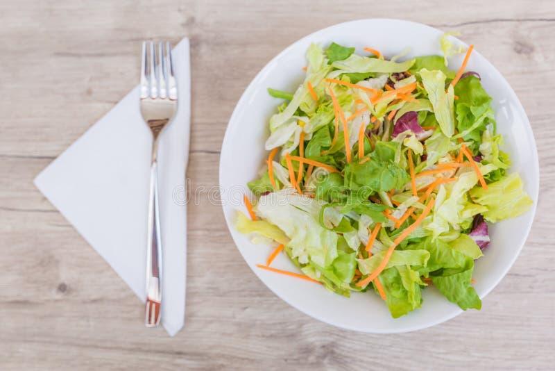 Свежий салат с томатами вишни, шпинатом, arugula, romaine и салатом в плите на белой деревянной предпосылке, взгляд сверху стоковая фотография