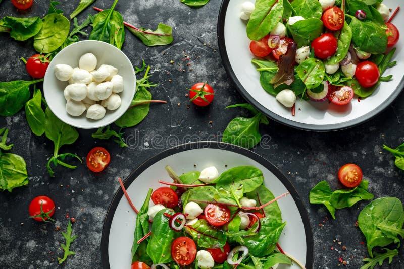 Свежий салат томата, моццареллы вишни с зеленым смешиванием салата и красный лук послуженный на плите еда здоровая стоковые изображения