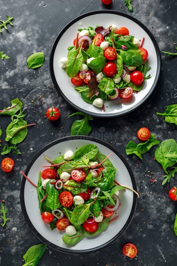 Свежий салат томата, моццареллы вишни с зеленым смешиванием салата и красный лук послуженный на плите еда здоровая стоковое изображение rf
