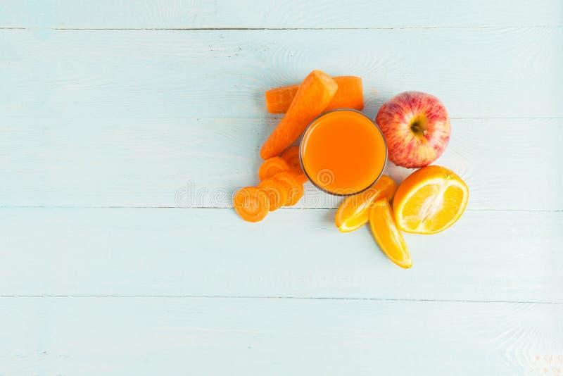 Свежий сок от морковей и оранжевых яблок в стекле на деревянной голубой предпосылке r r стоковые фото
