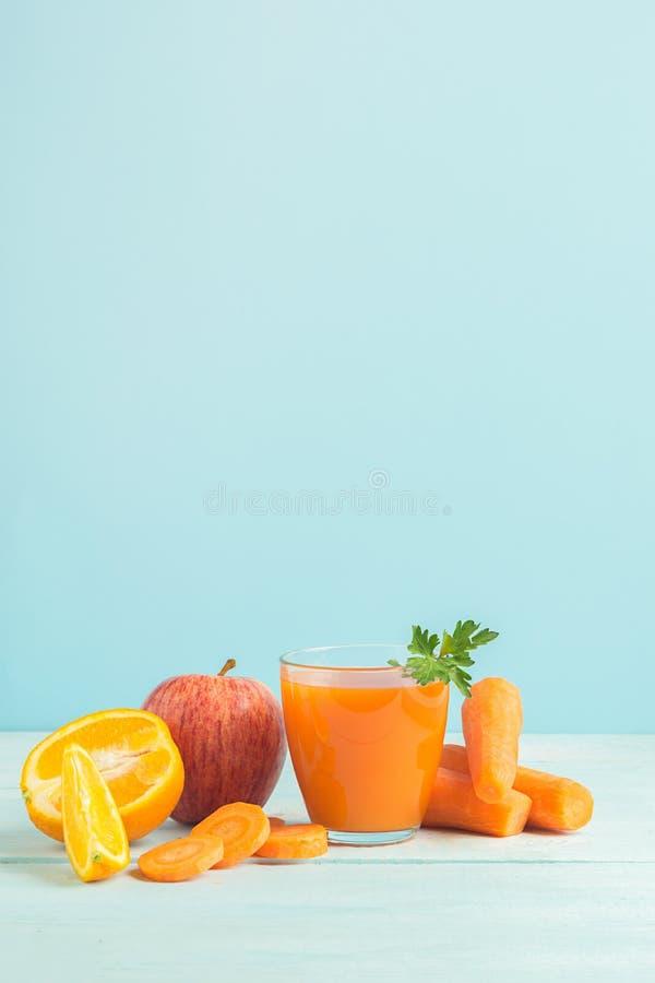 Свежий сок от морковей и оранжевых яблок в стекле на деревянной голубой предпосылке r r стоковые фотографии rf