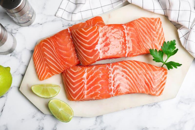 Свежий сырой лосось с лаймом и петрушкой на мраморном столе, плоская лежанка Рыбная деликатность стоковая фотография rf