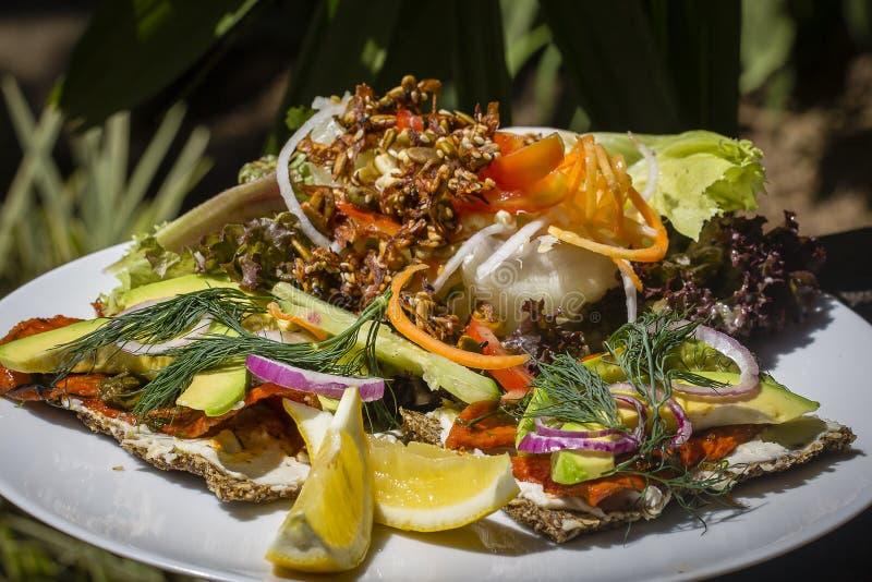 Свежий сырцовый салат от салата, avokado, томата, папапайи курил - семг с свежими травами и сандвичем норвежского gravlax стиля о стоковое фото rf