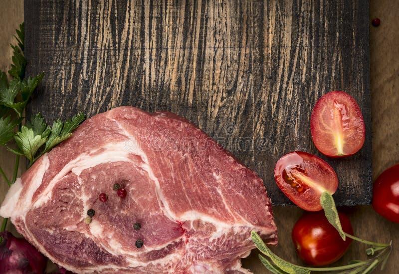Свежий сырцовый свинина с томатами и луками на разделочной доске на деревянном деревенском конце взгляд сверху предпосылки вверх стоковая фотография