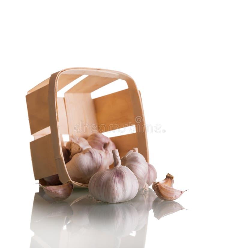 Свежий сырцовый чеснок в плетеной корзине изолированной на белой предпосылке стоковые изображения