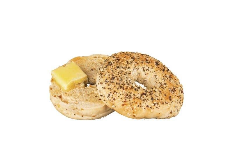 Свежий хлеб бейгл макового семенени с частью расплавленного масла стоковая фотография