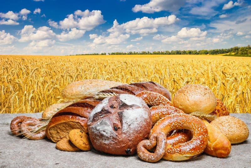 Свежий хлеб и хлебопекарня на пшеничном поле дерюги на фоне с облачным небом стоковое изображение rf