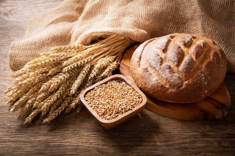 Свежий хлеб с ушами пшеницы и зерном на деревянном фоне стоковые изображения