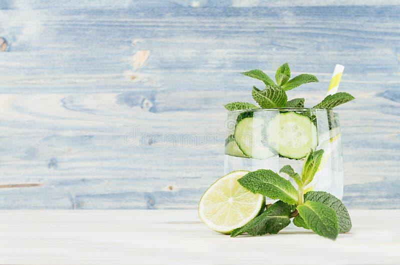Свежий холодный лимонад с минеральной водой, известкой, огурцом, мятой, льдом на свете - голубой деревянной планке стоковые изображения