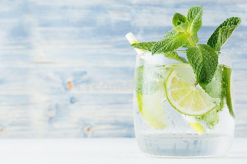 Свежий холодный напиток лета с известкой, мятой лист, соломой, кубами льда на свете - голубой деревянной предпосылке, крупном пла стоковые изображения