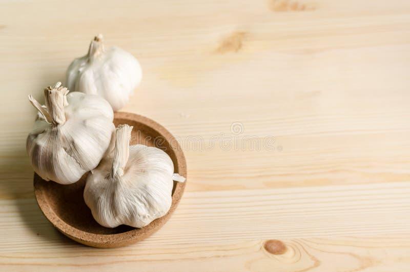 Свежий чеснок на белом деревянном столе, селективном фокусе стоковые фото