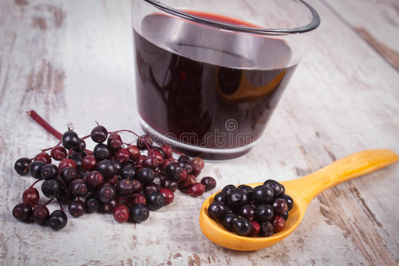 Свежий elderberry с деревянными ложкой и соком на старой деревянной предпосылке, здоровом питании стоковое изображение rf