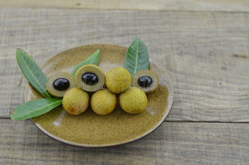 Свежий longan в коричневой плите на деревянном столе стоковое фото