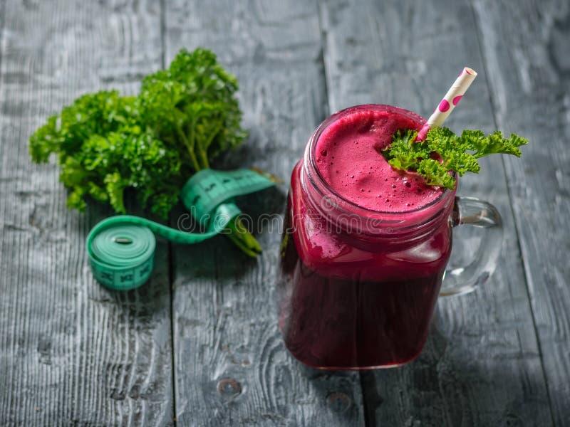 Свежий smoothie бураков, измеряя лента и петрушка на черном деревянном столе Концепция диетической естественной еды вегетарианска стоковое фото rf