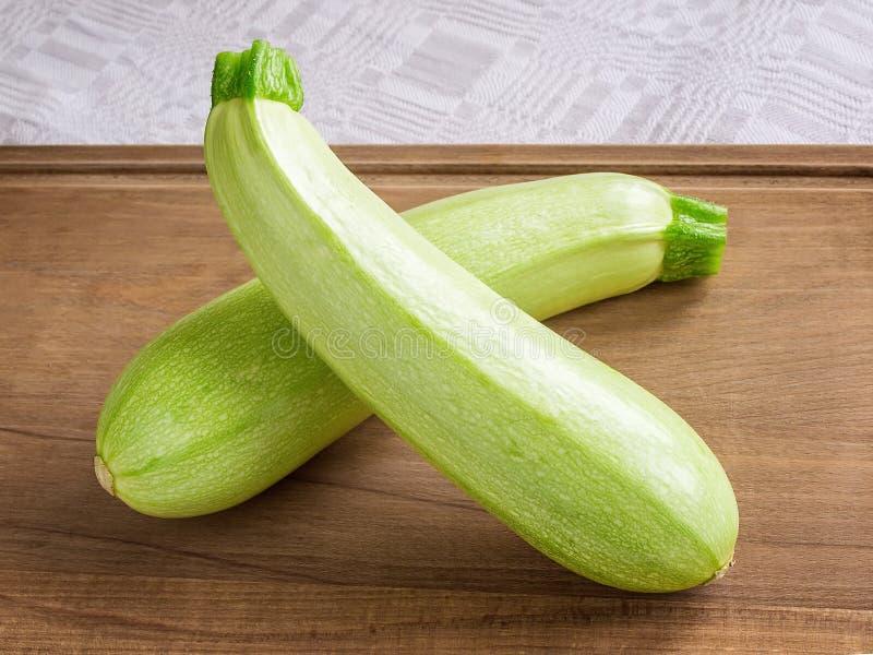 2 свежих зеленых courgettes или крис кросс цукини на коричневой деревянной разделочной доске Сварите дома Свежие овощи, вегетариа стоковая фотография rf
