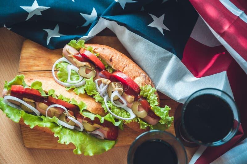 2 свежих хот-дога на деревянной доске, стеклах с колой и американском флаге стоковые фото