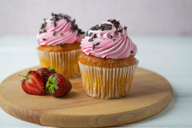 Свежо испеченные пирожные с замораживать и шоколадом клубники брызгают стоковое фото