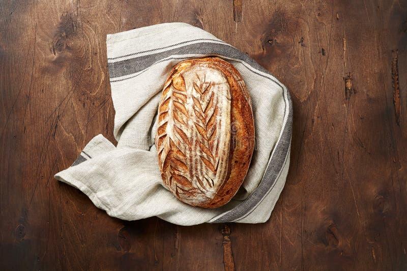 Свежо испеченные хлебцы хлеба sourdough ремесленника с полотенцем кухни на темной деревянной предпосылке стоковое фото rf
