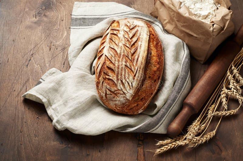 Свежо испеченные хлебцы хлеба sourdough ремесленника с шипом пшеницы и сумкой муки на темной деревянной предпосылке стоковые изображения