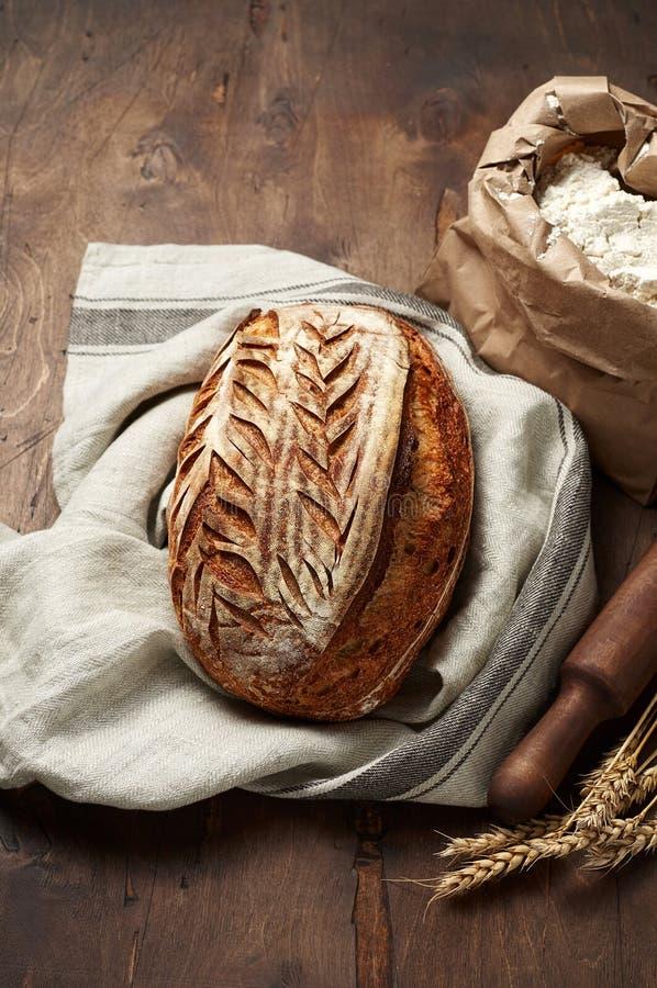 Свежо испеченные хлебцы хлеба sourdough ремесленника с шипом пшеницы и сумкой муки на темной деревянной предпосылке стоковая фотография